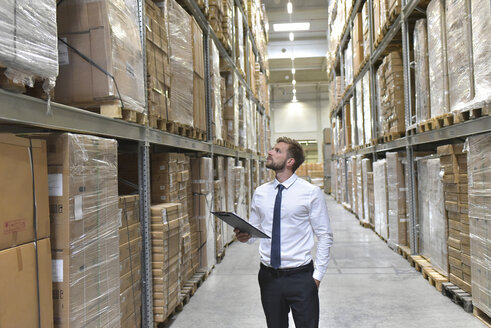 Businessman with clipboard in warehouse looking at shelves - LYF00770