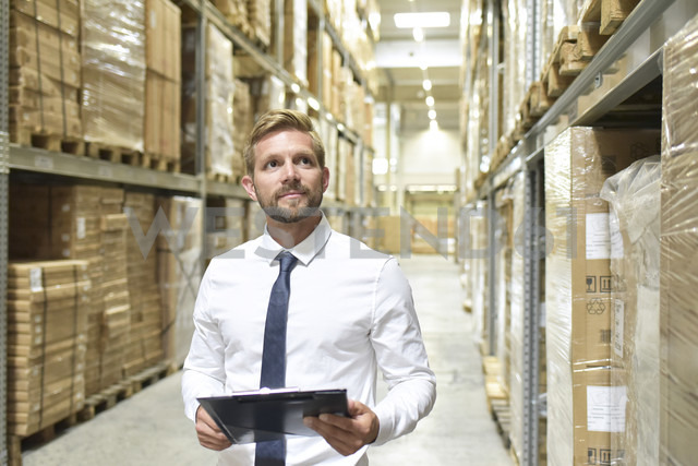 Businessman with clipboard in warehouse looking at shelves - LYF00773