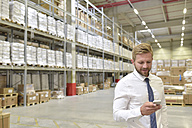 Smiling businessman looking at cell phone in warehouse - LYF00776