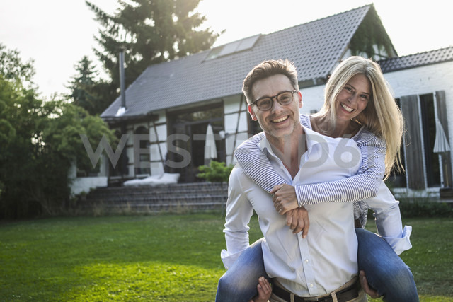 Portrait of happy mature couple on meadow in front of their house - RIBF00669 - Richárd Bellevue/Westend61