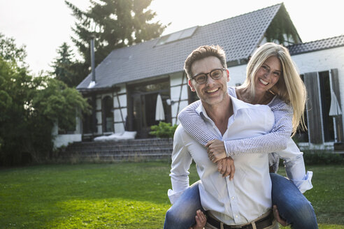 Portrait of happy mature couple on meadow in front of their house - RIBF00669