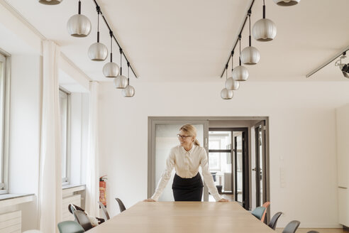 Smiling businesswoman standing in conference room - JOSF01369
