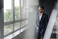 Businessman in office looking out of window - JOSF01375