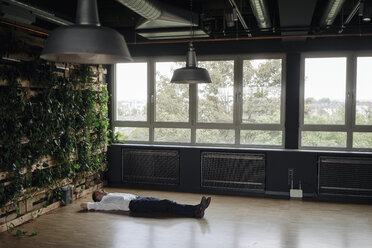 Businessman in green office lying on the floor - JOSF01381