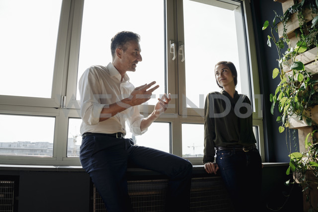 Businessman and businesswoman talking at the window - JOSF01390