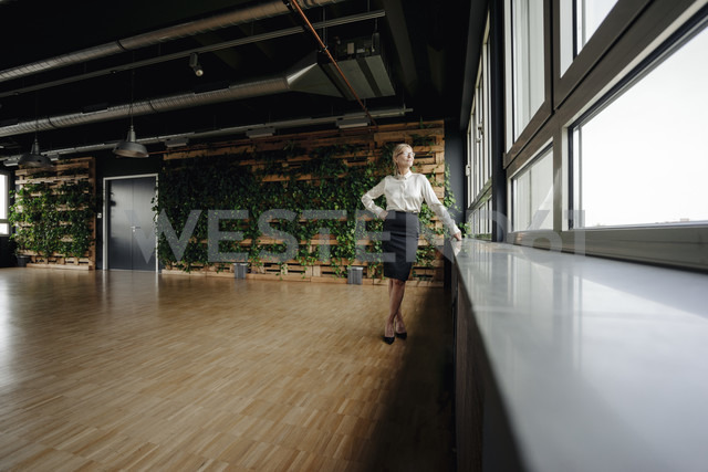 Businesswoman in green office looking out of window - JOSF01402