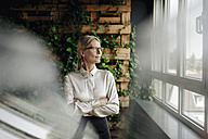 Businesswoman in green office looking out of window - JOSF01405