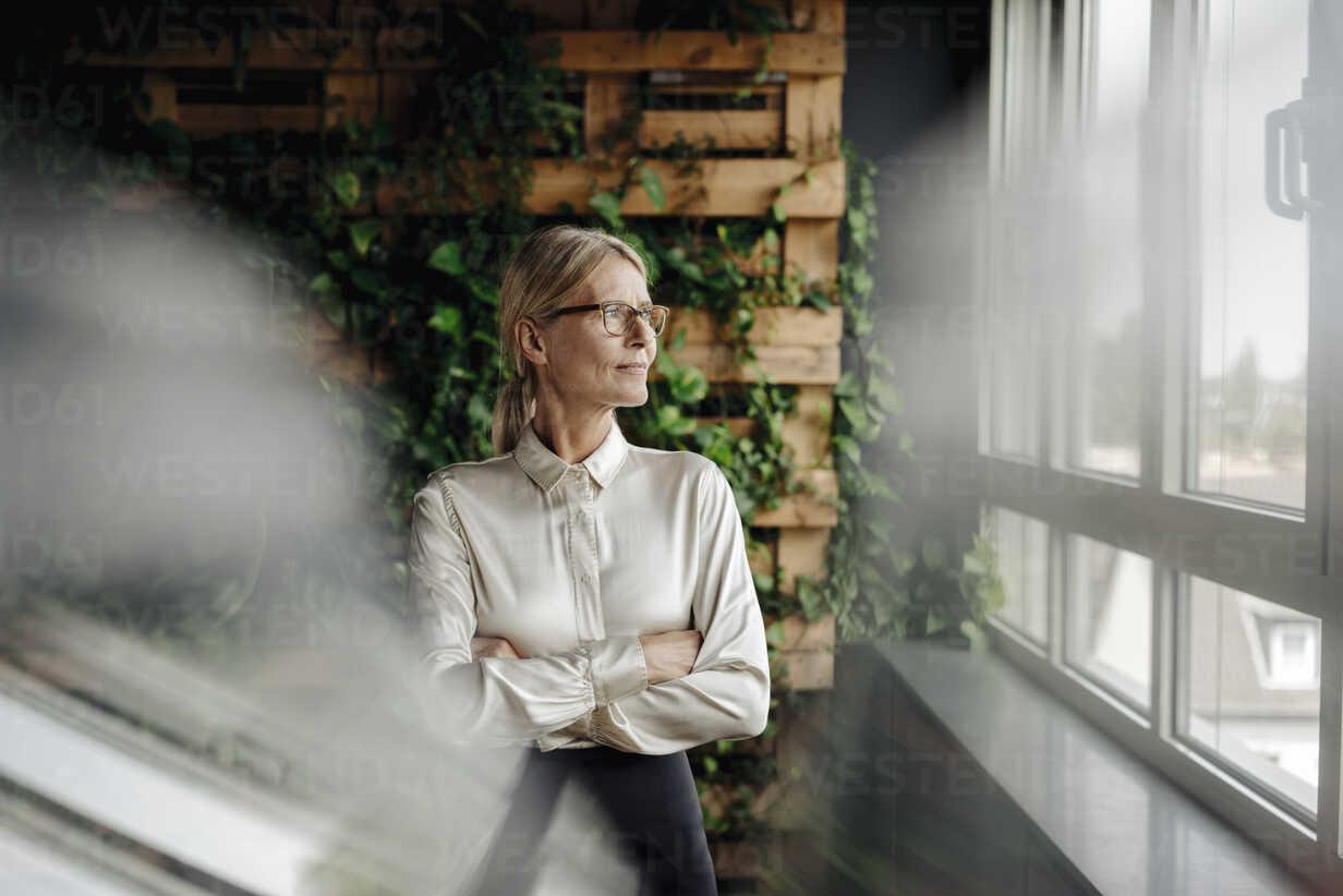 Businesswoman in green office looking out of window - JOSF01405 - Joseffson/Westend61