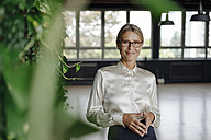 Portrait of confident businesswoman in green office - JOSF01417