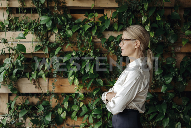 Businesswoman at wall with climbing plants - JOSF01420 - Joseffson/Westend61