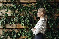 Businesswoman at wall with climbing plants - JOSF01420