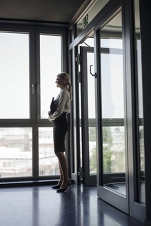 Businesswoman in office looking out of window - JOSF01429
