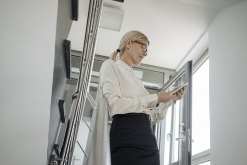 Businesswoman in office looking at tablet - JOSF01432