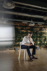 Businessman sitting on chair in green office looking at cell phone - JOSF01438