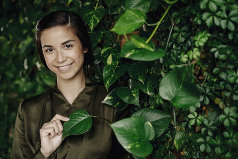 Portait of smiling young woman at wall with climbing plants - JOSF01450