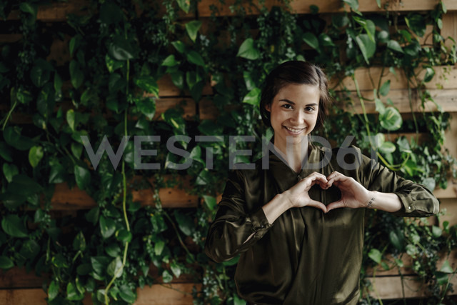 Portait of smiling young woman shaping heart at wall with climbing plants - JOSF01453