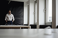 Businessman in office looking out of window - JOSF01480
