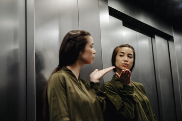 Young woman looking in mirror in elevator blowing a kiss - JOSF01486