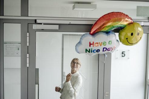Businesswoman on corridor holding balloon - JOSF01489
