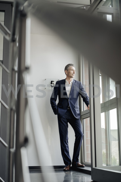 Businessman in office looking out of window - JOSF01492