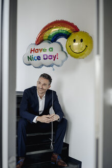 Smiling businessman sitting on stairs holding balloon - JOSF01495