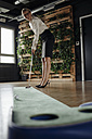 Businesswoman playing golf in office - JOSF01513