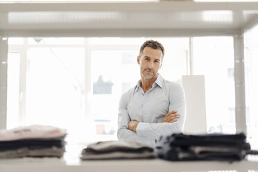 Portrait of confident businessman standing at shelf with clothes - KNSF02423