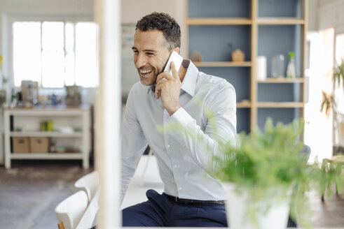 Happy businessman in office on cell phone - KNSF02426