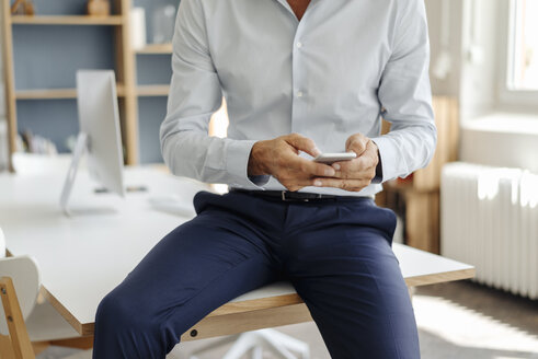 Close-up of businessman in office using cell phone - KNSF02429