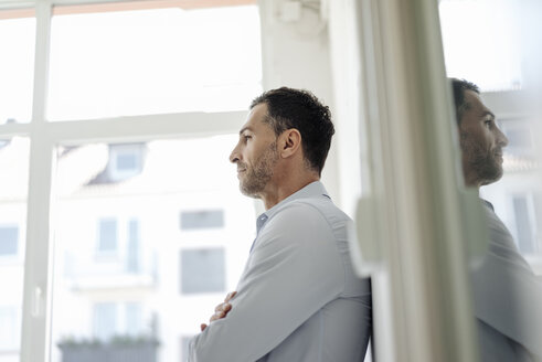 Businessman in office leaning against wall at the window - KNSF02432