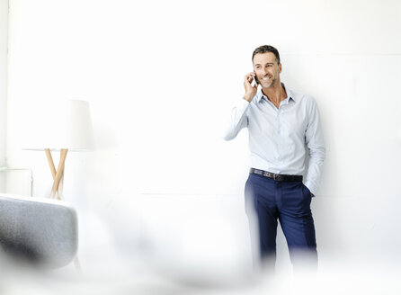 Smiling businessman in office on cell phone - KNSF02435