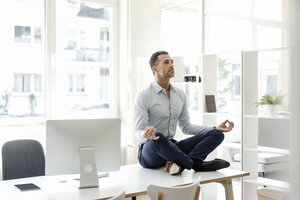 Businessman sitting on table in office practising yoga - KNSF02438