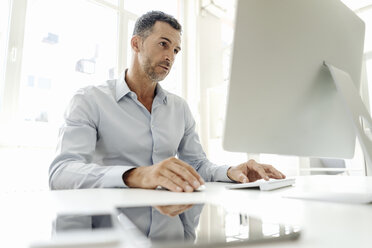 Businessman using computer at desk in office - KNSF02441