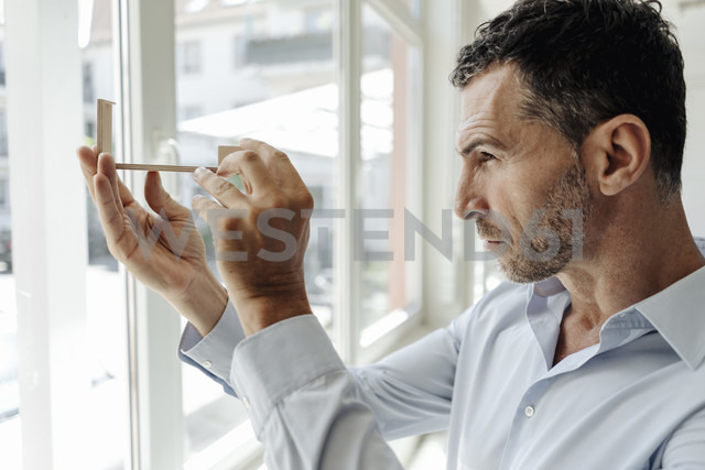 Businessman at the window looking at architectural model - KNSF02453