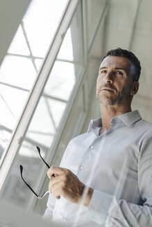 Businessman holding glasses standing at the window - KNSF02456