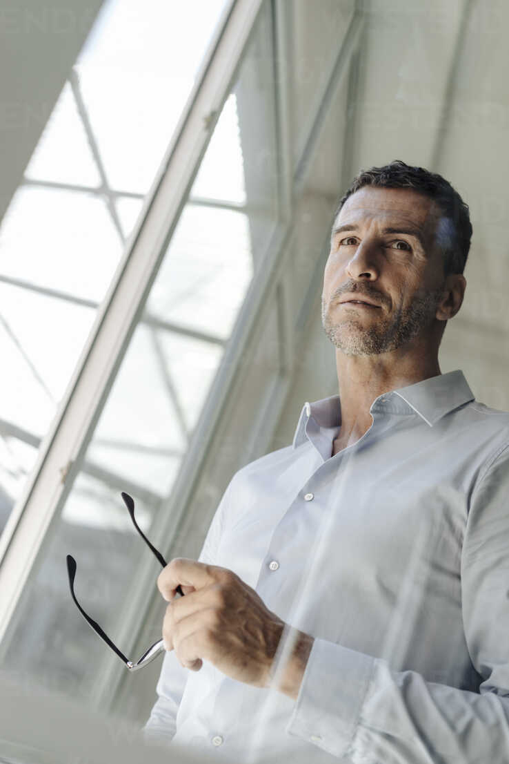 Businessman holding glasses standing at the window - KNSF02456 - Kniel Synnatzschke/Westend61