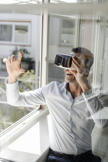 Businessman at the window wearing VR glasses - KNSF02462
