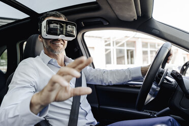Businessman wearing VR glasses driving a car - KNSF02471