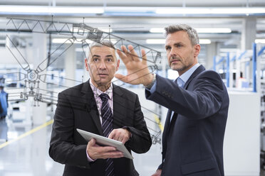Two businessmen looking at graphic on glass pane in factory hall - DIGF02772