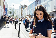 UK, London, Portobello Road, smiling woman looking at cell phone - MGOF03574