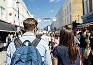 UK, London, Portobello Road, back view of couple on shopping spree - MGOF03583