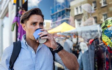 UK, London, Portobello Road, portrait of man drinking coffee in front of a shop window - MGOF03586