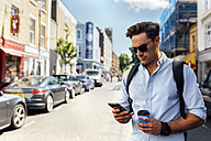 UK, London, Nottinghill, man looking at smartphone - MGOF03592