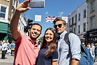 UK, London, Portobello Road, portrait of three friends taking selfie with smartphone - MGOF03595