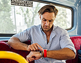 UK, London, man sitting in a double decker bus using smartwatch - MGOF03598