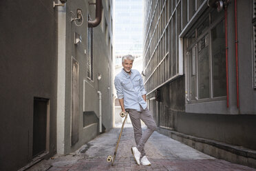 Mature man with longboard in an alley - WESTF23557