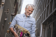 Mature man with longboard in an alley - WESTF23560