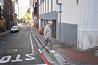 Mature man walking in the city, carrying bag - WESTF23569