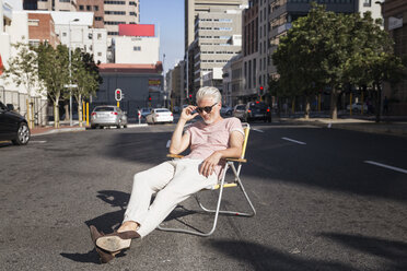 Mature man sitting on chair in the street, wearing sunglasses - WESTF23572