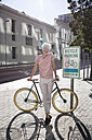 Mature man in the city leaning on his bicycle - WESTF23581